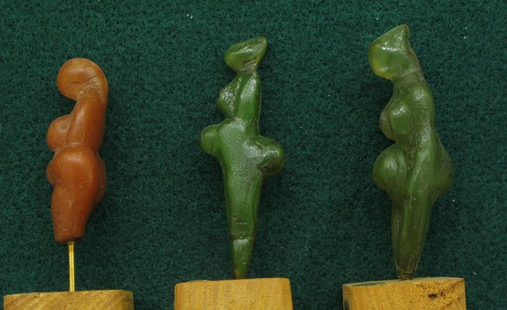 """Au centre, statuette en stéatite verte dite """"Polichinelle"""" découverte dans les grottes de Grimaldi (Ligurie/Italie). Gravettien vers 25000 BP - H=6 cm"""